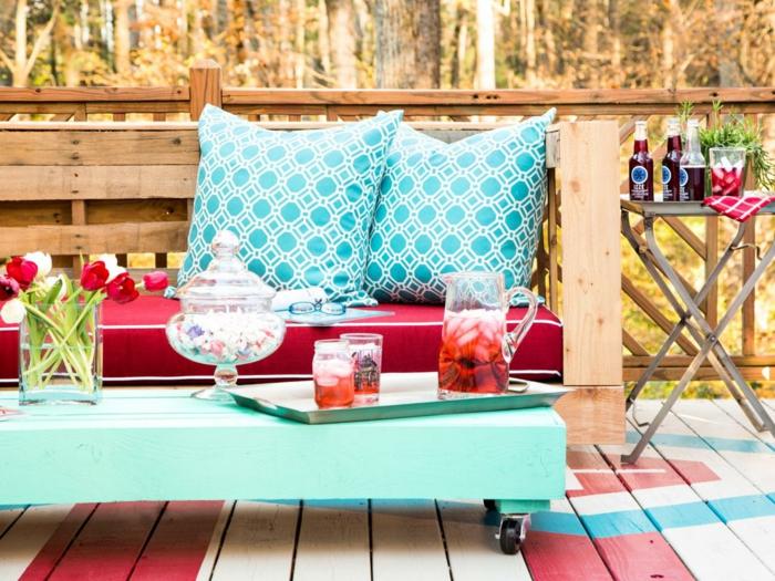 banc en palette, canapé palette, table basse en vert réséda avec des petites roues noires, grands coussins carrés en vert menthe et blanc