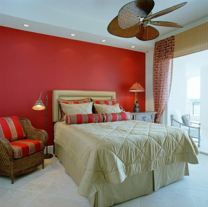 chambre à coucher déco sérène, mur rouge, fauteuil tressé, spots encastrés, grand lit blanc