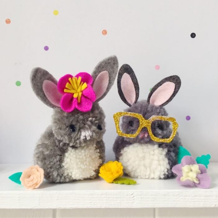 couple de lapins doudou fabriqués en pompons de laine et décorés avec accessoires chic en forme de lunettes et couronne florale pour la tete
