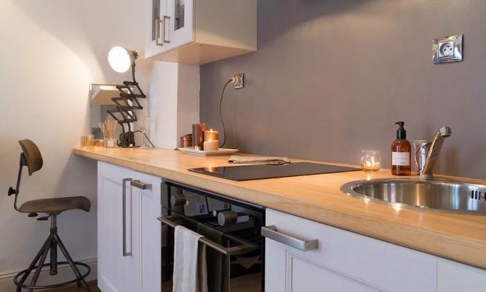 modèle de cuisine grise et bois avec pan de mur de nuance gris clair combiné avec armoires bas en blanc et four noir