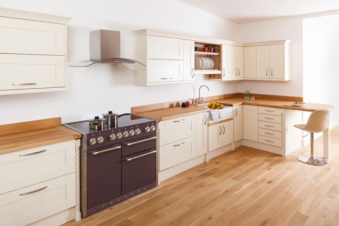 modèle de cuisine propre aménagée dans l'esprit minimaliste avec four noir mate et meubles blancs à poignées métalliques