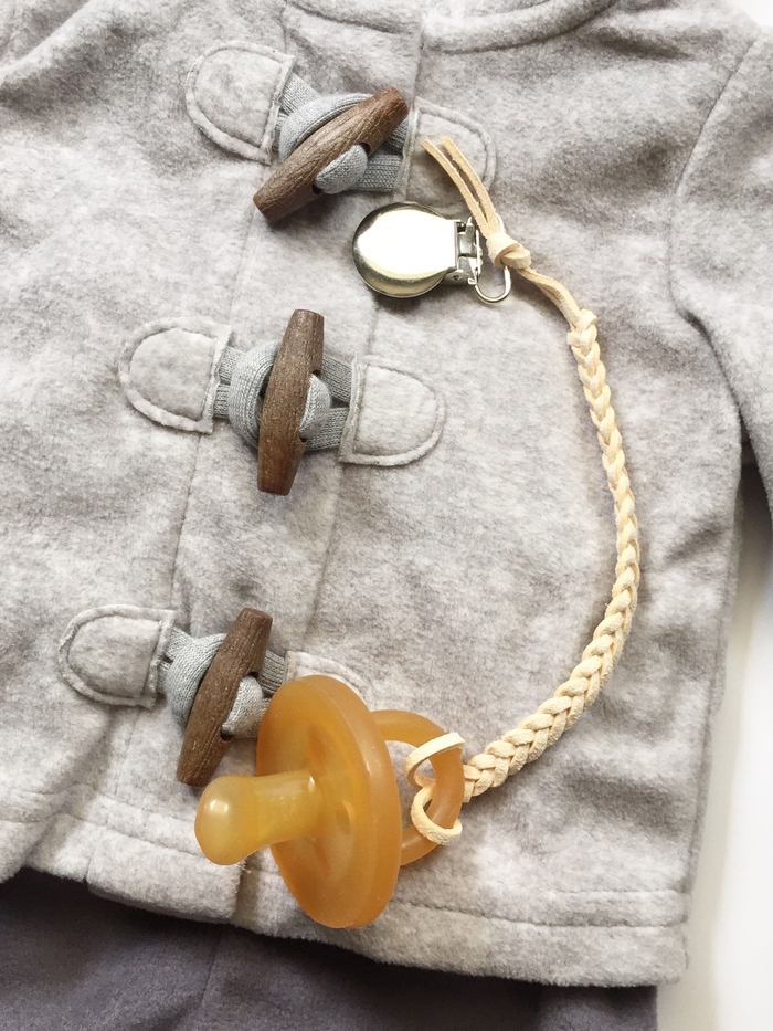un accroche-tetine tressé en cuir au design sobre et épuré qui s'associe à merveille avec toutes les tenues de bébé