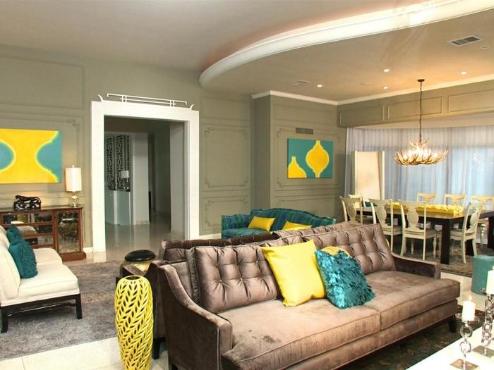 séjour contemporain, canapé en couleur taupe, plafond suspendu ondulant, coussins déco jaunes et bleus