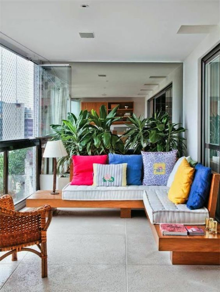 meuble d'angle en bois couleur cerise, coussins colorés, dalles en gris clair, fauteuil en rotin couleur cerise, idee deco terrasse, idee amenagement terrasse