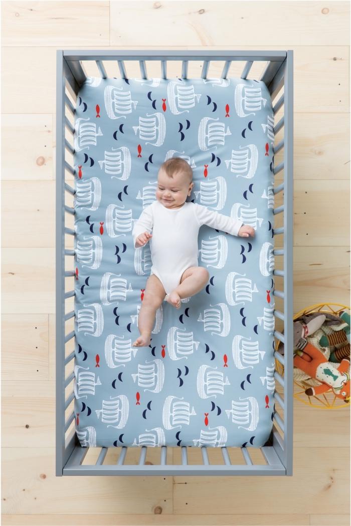 couverture de lit bleu clair avec bateaux blancs pour un linge de lit dans la chambre nouveau-né au plancher de bois clair et lit bébé gris clair