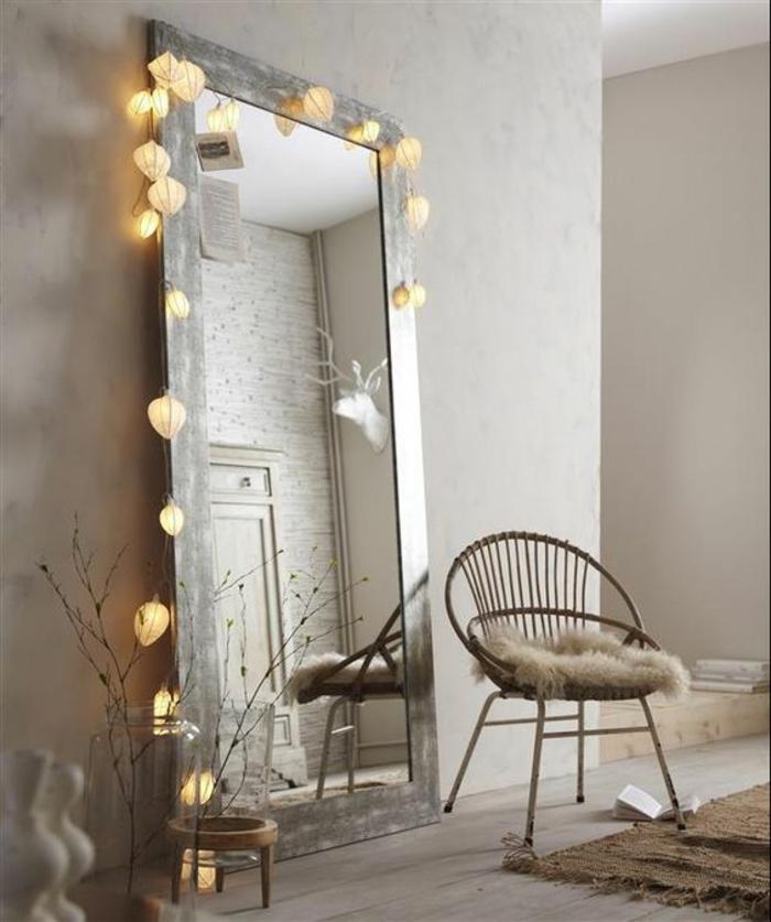 déco murale avec un grand miroir au cadre couleur argent, orné d'une guirlande lumineuse de lanternes boules blanches, style de pièce minimaliste, fauteuil en métal au dossier rond, tapis couleurs terre