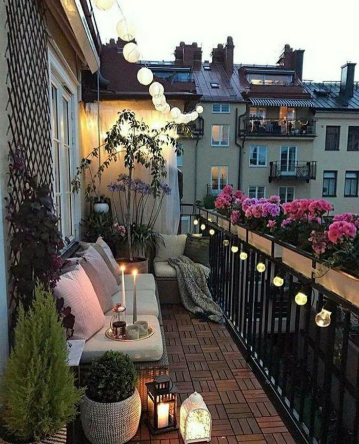 balcon illuminé avec des guirlandes d'ampoules en verre et des boules lanternes, idee amenagement terrasse, canapé avec des coussins couleur claire, sol recouvert de dalles en terre cuite, garde-corps décoré de pots rectangulaires avec des fleurs roses