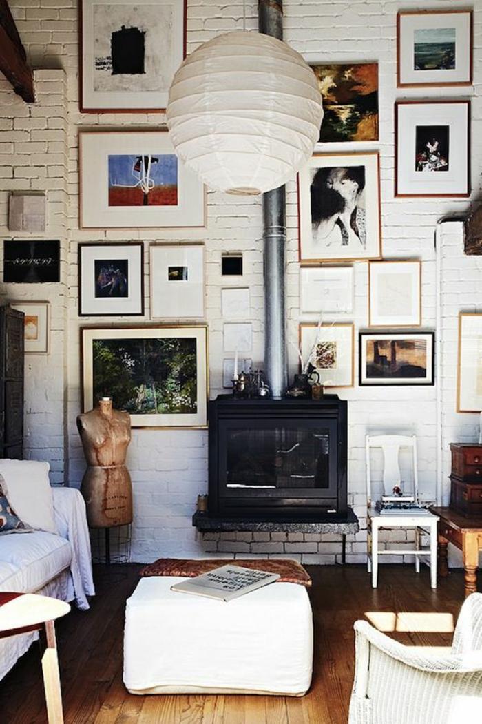 déco murale avec des photos et des dessins, mur en briques blanches entièrement recouvert d'oeuvres d'art, habiller un mur d'art, parquet en beige, cheminée en métal noir, luminaire lanterne en carton blanc en style asiatique, tabouret carré en simili cuir blanc