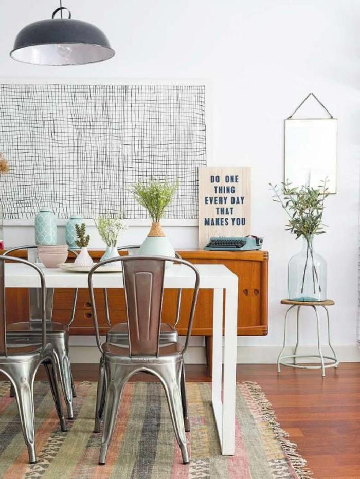 tapis mural avec effet tressé en noir et blanc, panneau décoratif sur mur blanc total, miroir style vintage tout simple, accroché sur une punaise avec une corde, déco style industriel, quatre chaises métal couleur argent rétro, tapis coloré en vert réséda et rose aux rayures verticales, un pan de mur