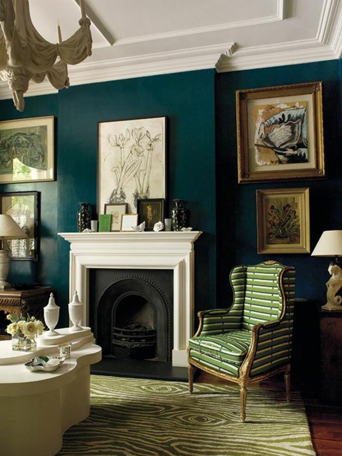mur peint en bleu canard, plafond blanc avec des frises classiques, tableaux aux cadres dorés, habiller un mur de manière artistique, tapis vert réséda aux motifs troncs d'arbres