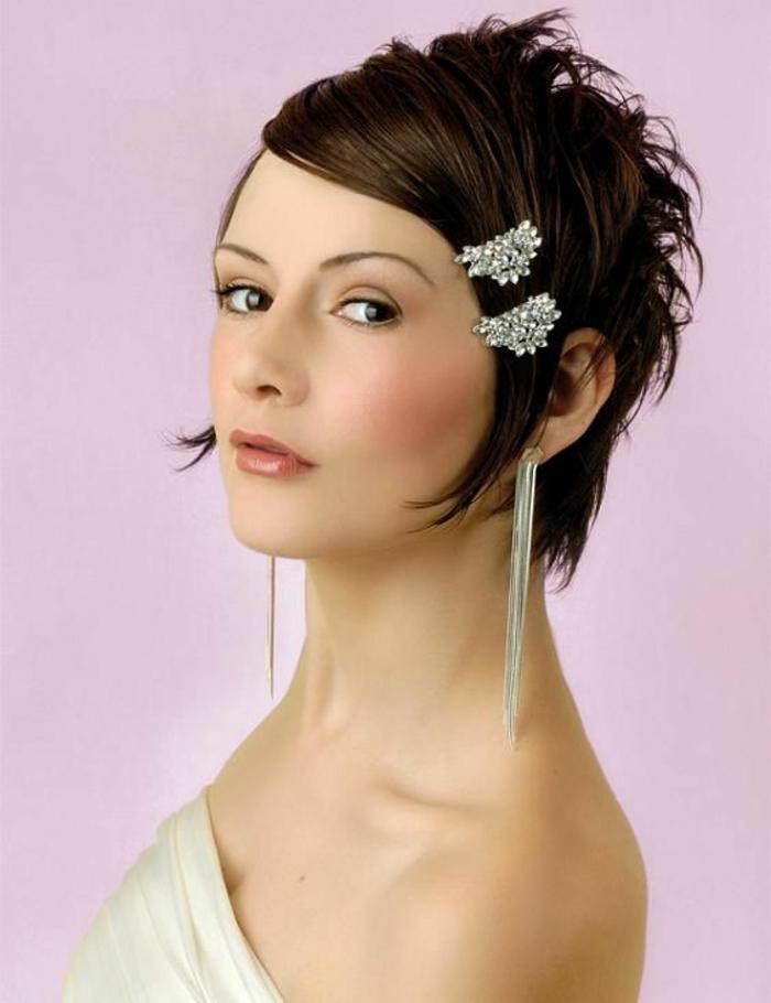 ideée coiffure mariage, coiffure mariage vintage, années 30, look glamour et sensuel, deux petites barrettes recouvertes de pierres blanches posées de coté, deux boucles d'oreilles longues en argent touchant les épaules