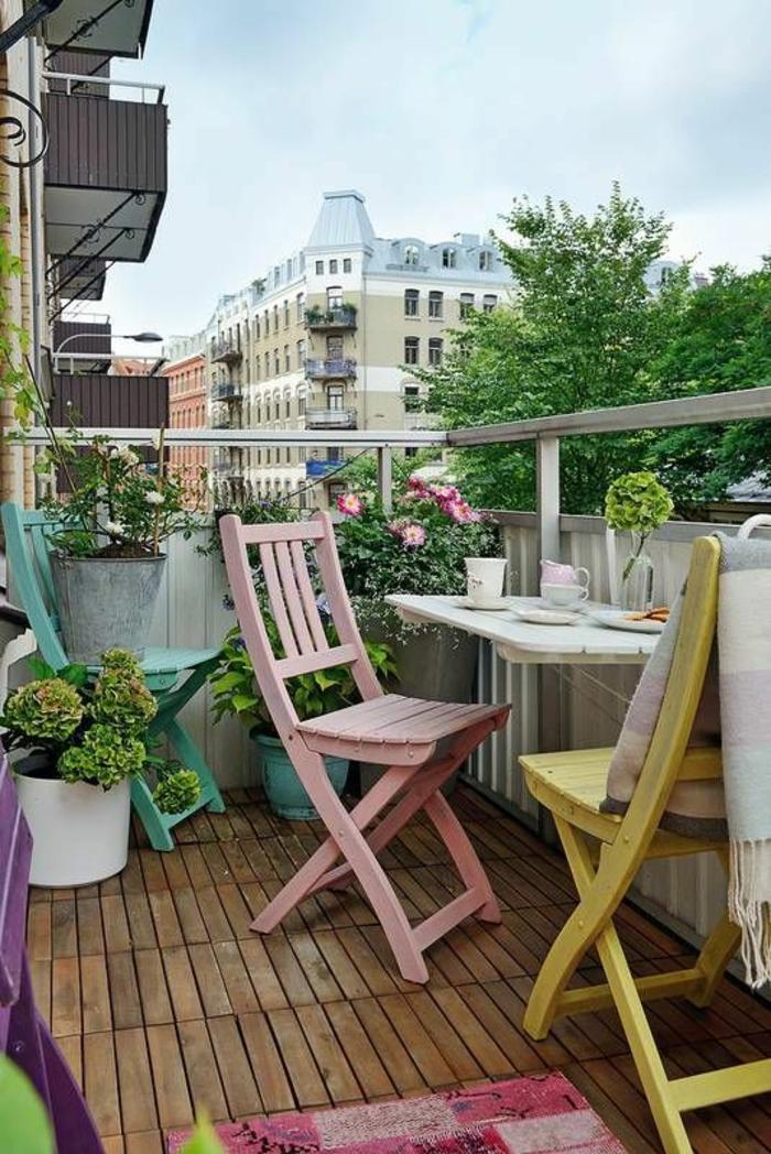 balcon fleuri, pots de plantes et fleurs rouges et roses, idée déco terrasse, meubles pliables en bois colorés en rose bonbon, jaune et vert menthe, table pliable sur le garde-corps en bois peint en blanc, sol terrasse recouvert de planches en bois