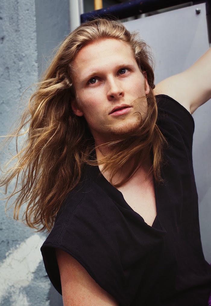 coupe cheveux long homme blond avec tee shirt col v noir