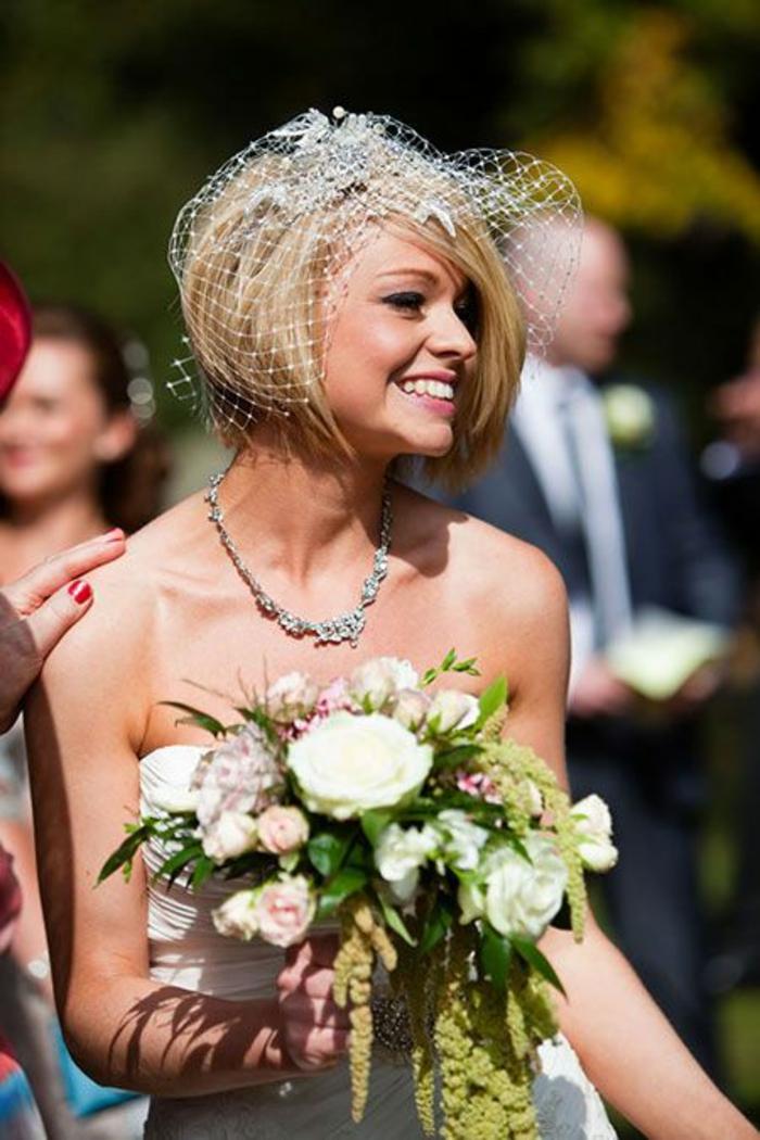 coiffure mariage cheveux court, bob court et blond, coupe asymétrique, coiffure mariee, look sexy, robe bustier épaules nues, diadème avec voilette en gris clair métallique