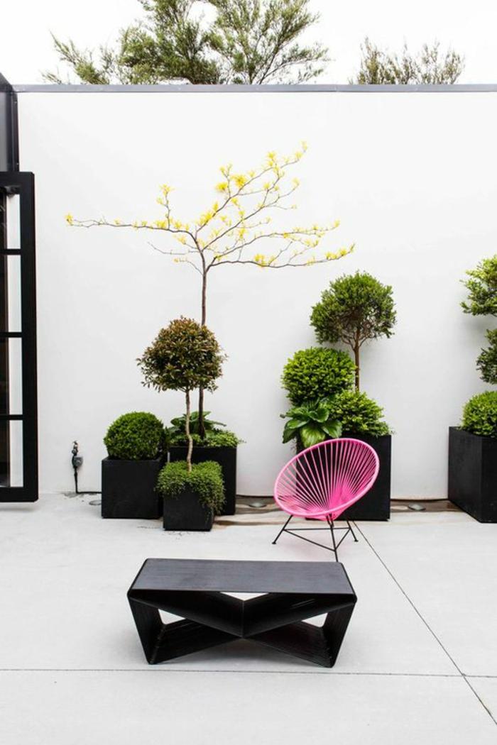 idee deco terrasse, decoration terrasse exterieur, fauteuil en fil tressé rose bonbon, table basse noire, pots noirs carrés avec des arbres verts, carrelage blanc