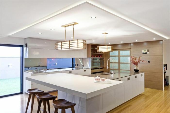 cuisine avec ilot élégante, îlot de cuisine blanc, chaises en bois, faux plafond lumineux, sol stratifié
