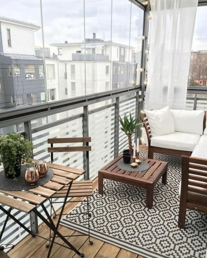 aménagement terrasse appartement, idée déco terrasse, tapis motifs graphiques en noir et blanc, table et chaises IKEA pliables, canapé de jardin massif d'angle, voilages blancs