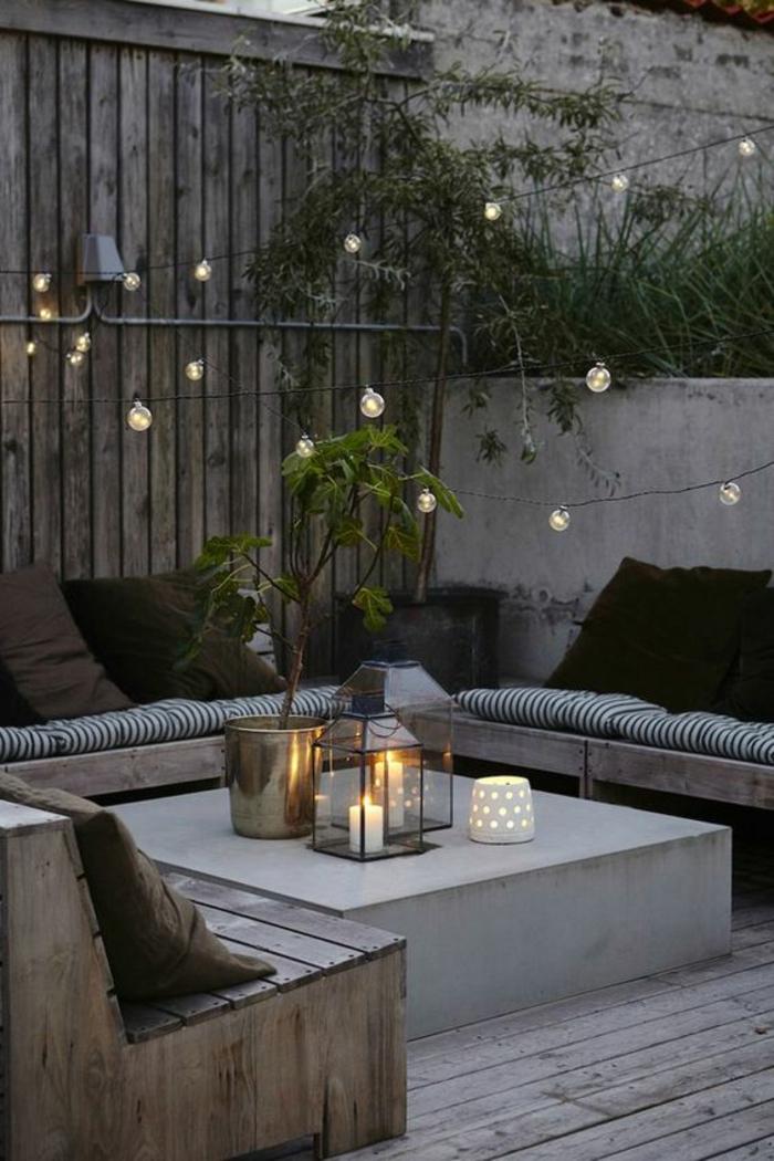 decoration terrasse exterieur, decoration jardin terrasse, table basse carrée, guirlande lumineuse, banc en bois avec des coussins sur le dossier, sol recouvert de bois gris, lanternes et bougeoirs en style marocain