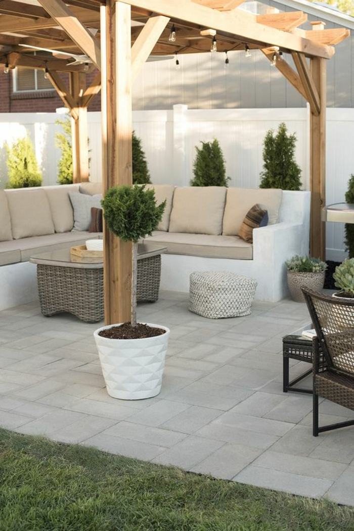 pergola en bois clair, idée déco terrasse, pot blanc avec arbre vert, dalles couleur blanc crème, decoration jardin terrasse, meubles en rotin marron clair, grand canapé d'angle en blanc avec des coussins couleur ivoire