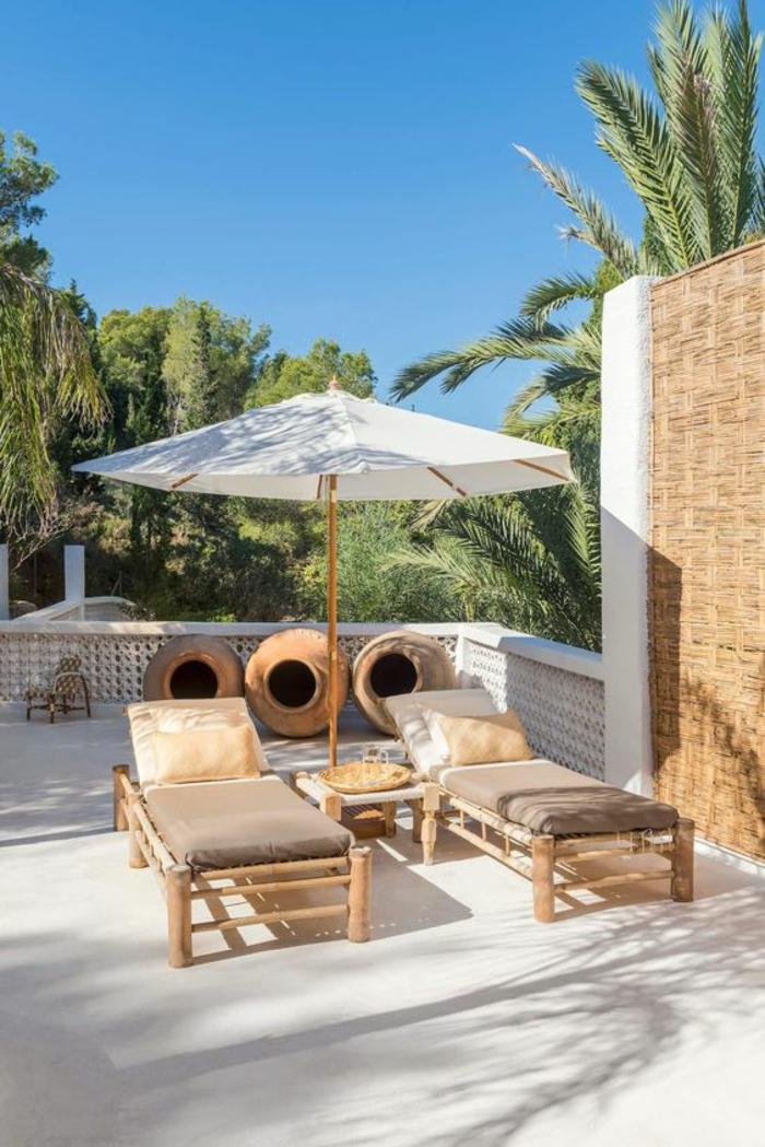 deux chaises-longues en bois beige recouverts de matelas en marron et doré, parasol tissu blanc et bois, idée déco terrasse en style méridional avec des palmiers