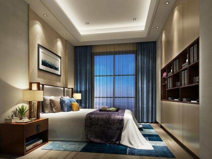 tapis bleu et bibliothèque intégrée dans une chambre feng shui, rideaux bleus