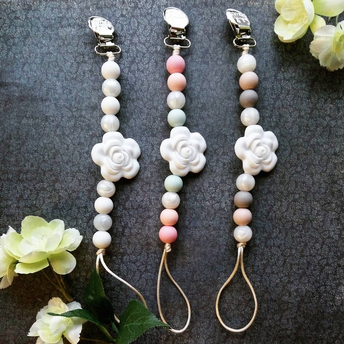 modèle d'attache tétine personnalisée raffiné et doux réalisé avec des perles en tons pastel, décoré d'une jolie fleur blanche au milieu de la chaîne