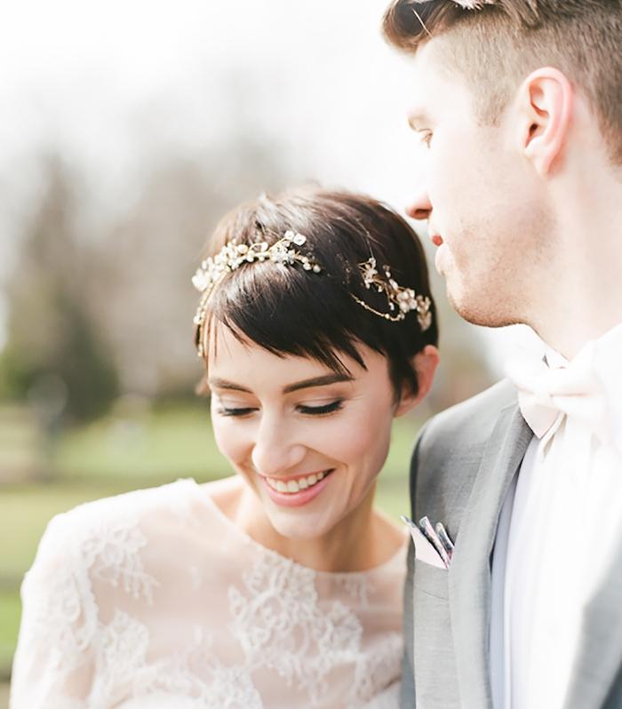 pixie avec des mèches plus longues couvrant une partie du visage et bijou de cheveux couronne za motifs fleuris et petites pierres, robe de mariée blanche dentelle