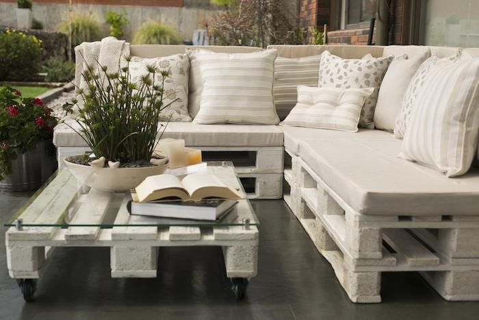 modèle de canapé en palette blanchi avec coussins beige, gris et blanc, table basse en palette avec plateau en verre à roulettes