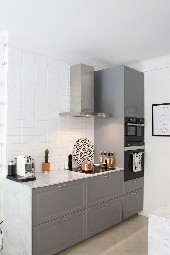 cuisine grise et blanche au design élégant associant des meubles à façades grises avec des poignées dorées et un comptoir en marbre