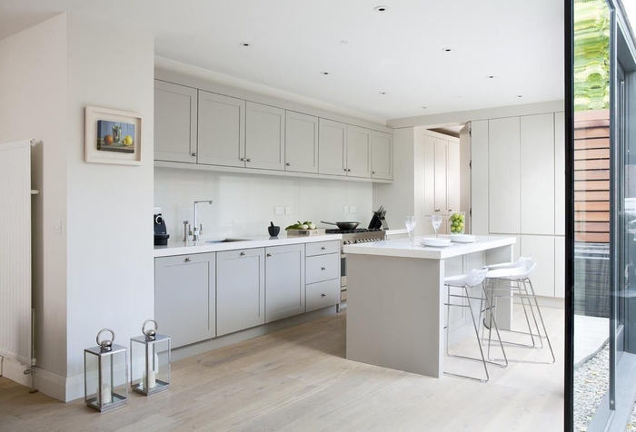 une cuisine gris clair monochrome ouverte sur une véranda et baignée de lumière