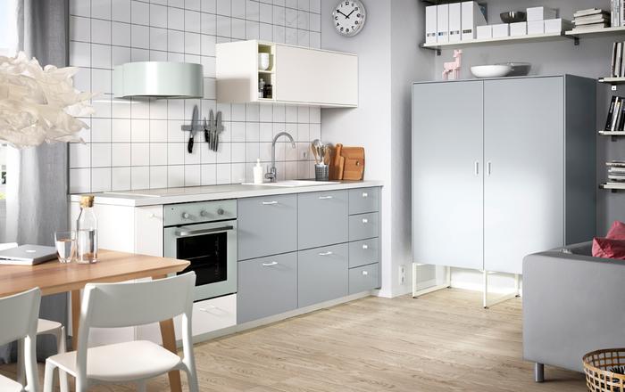 cuisine blanche et grise de style scandinave qui ne manque pas de charme grâce au carrelage mural blanc, les accents vert menthe et le luminaire design