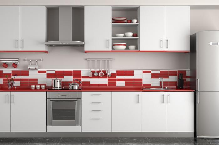 une cuisine grise et rouge aménagée en longueur avec une crédence originale en carrelage rouge et blanc