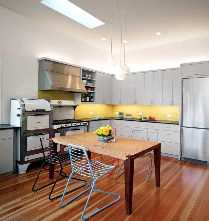 une cuisine grise moderne aux accents colorés et industriels égayée par une crédence jaune et le coin repas d'esprit bistrot