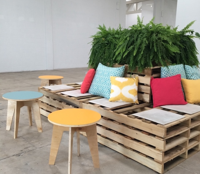 exemple de canapés en palettes autour d une grosse plante verte, coussins décoratifs colorés, tabourets bois