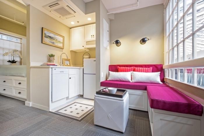 aménager un petit appartement aux murs beige avec mobilier de couleur vibrante en forme de canapé d'angle rose fuchsia