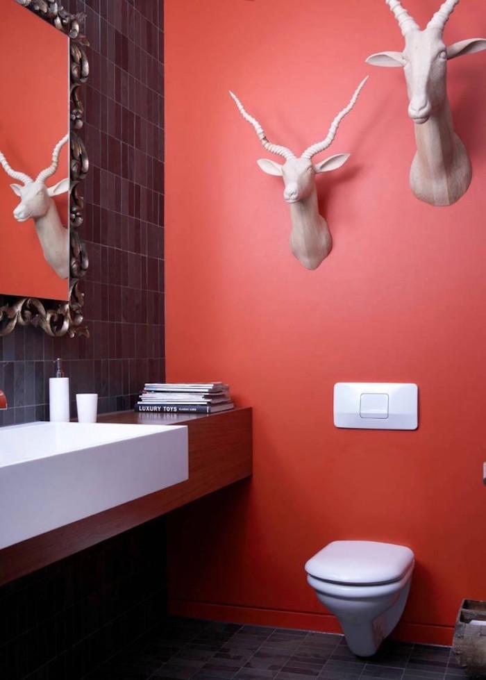 peinture toilettes idée couleur rouge clair avec tete de gazelle artificielle