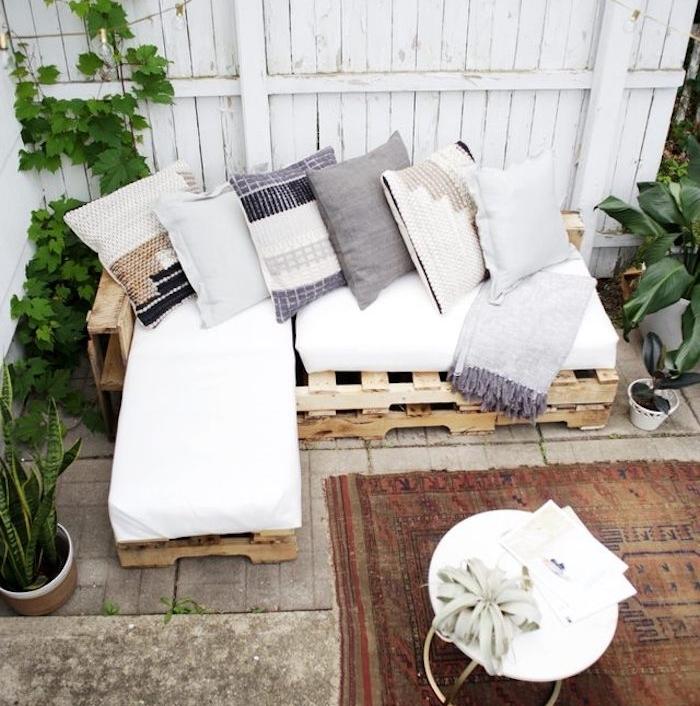 canapé en palette d angle avec des coussins d assise blanches et coussins décoratifs en gris, blanc et beige, table basse originale