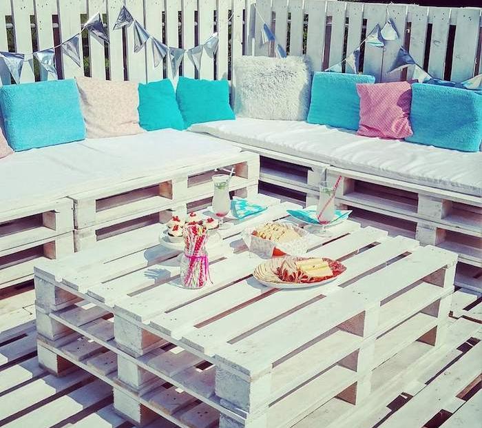 meubles de jardin en palettes de bois blanches canapé et table palette sur une terrasse en palette blanche, coussins décoratifs blanc, bleu et rose