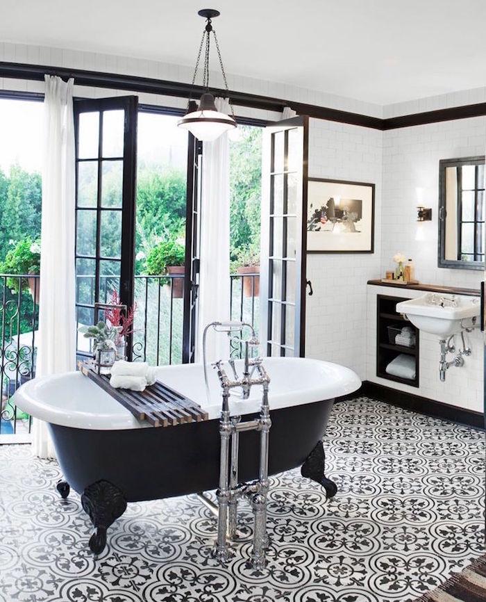 déco de salle de bain noir et blanc style rétro avec fenetre et baignoire noire en ilot sur carrelage graphique