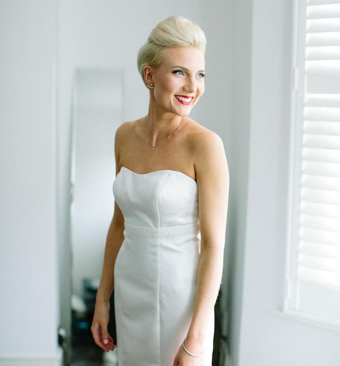 coiffure simple et rapide de mariée avec volume sur le dessus de cheveux colorés en blond polaire, robe de mariée blanche simple épurée