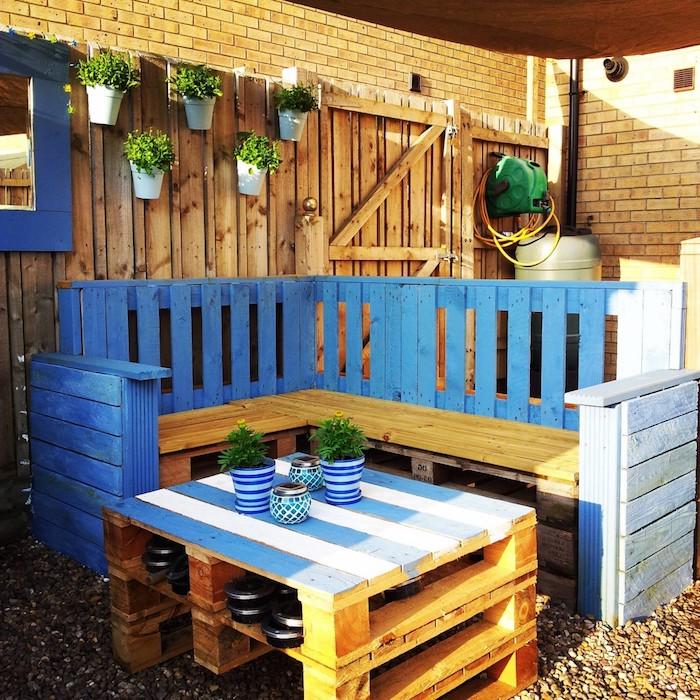 petit coin repos en plein air avec table basse de palettes superposés avec plateau repeint en blanc et bleu, banquette palette d angle en beige et bleu, deco pots de fleurs