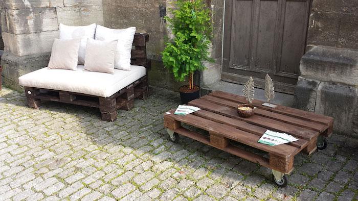 exemple comment fabriquer un fauteuil en palette avec coussins blanc et gris clair, table à café palettes à roulettes, plante verte