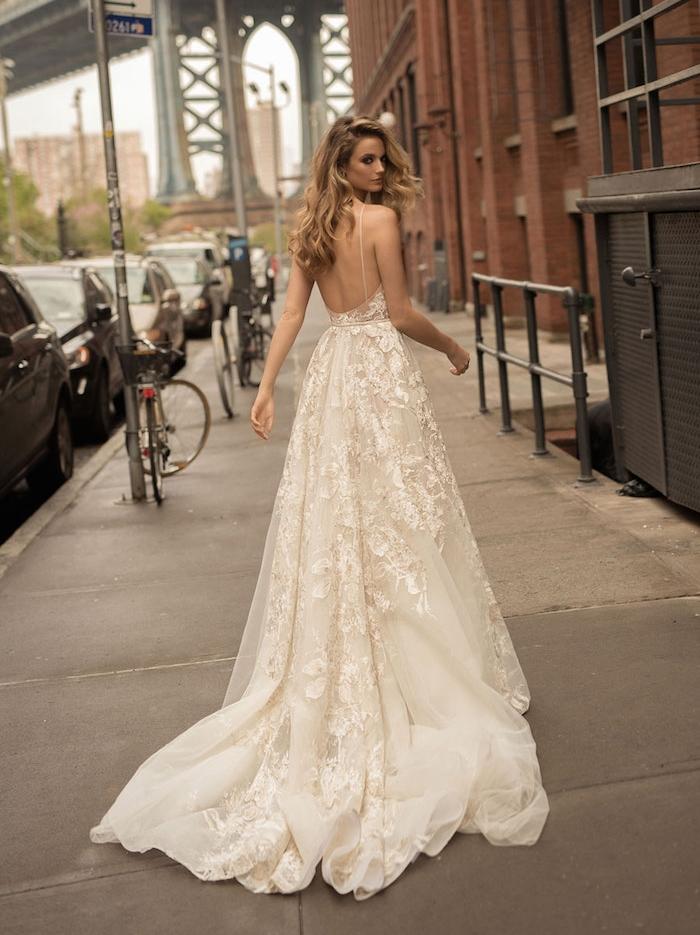 robe de mariée 2018 avec une longue traine et des fleurs brodées, dos nu et bretelles fines, couleur blanc cassé et ivoire