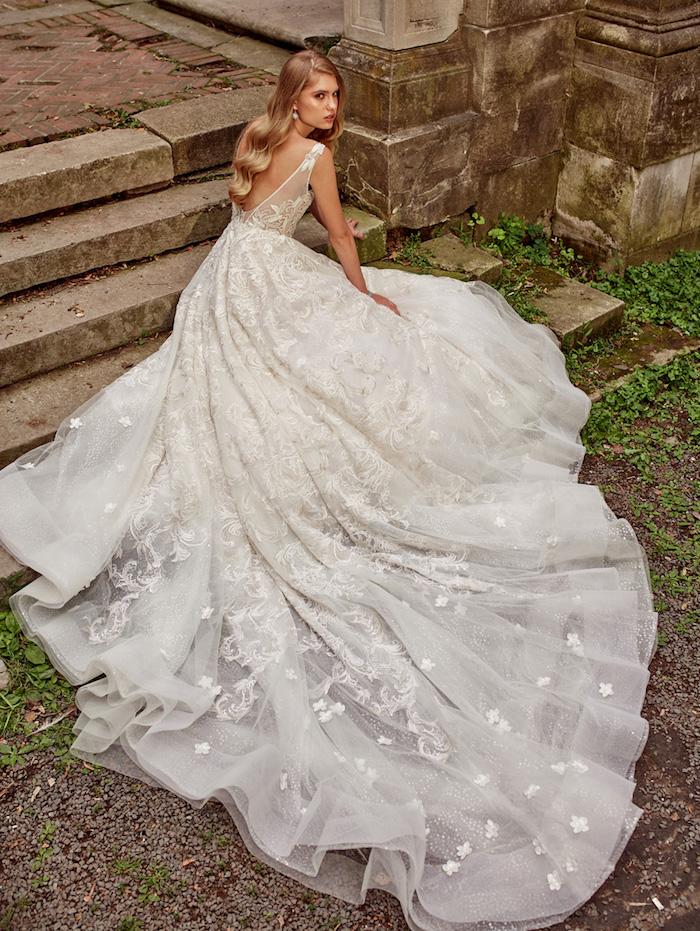 princesse robe de mariée longue avec une longue traine à motifs floraux, fleurs blanches brodées et un top transparent