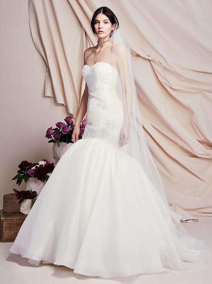 modèle de robe de mariée sirène avec un bas évasé et un hait blanc avec de petites décorations et voiles blanche longue