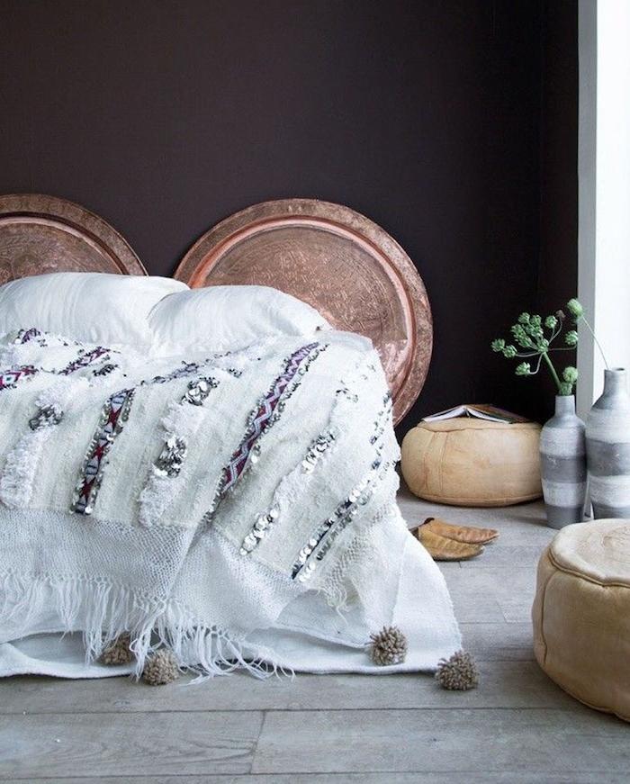 linge de lit blanc cassé, mur noir décoré de rondins bois, parquet gris, poufs beiges, vase blanc et gris, deco chambre tete de lit orientale