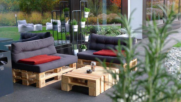 modèle de table basse palette de bois avec fauteuil en palette couvert de coussin gris, support pots de fleurs noir en métal