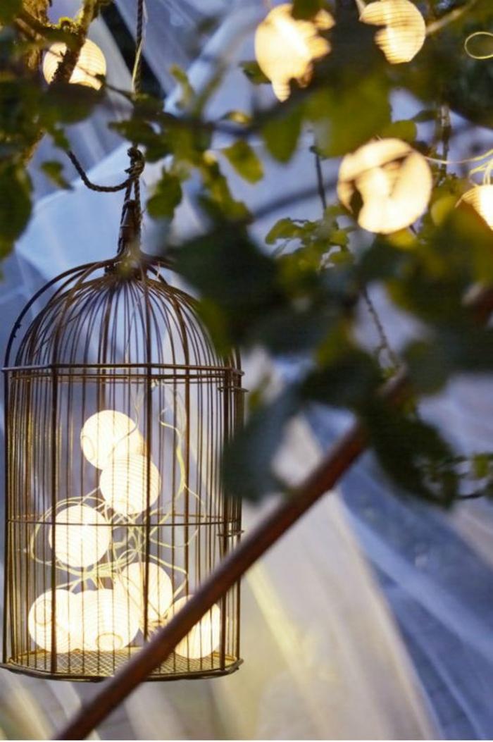 cage d'oiseaux utilisée pour contenir des boules blanches qui sont des éléments d'une guirlande lumineuse, accrochée partiellement aux branches d'un arbre, décorer son jardin en créant des effets lumineux