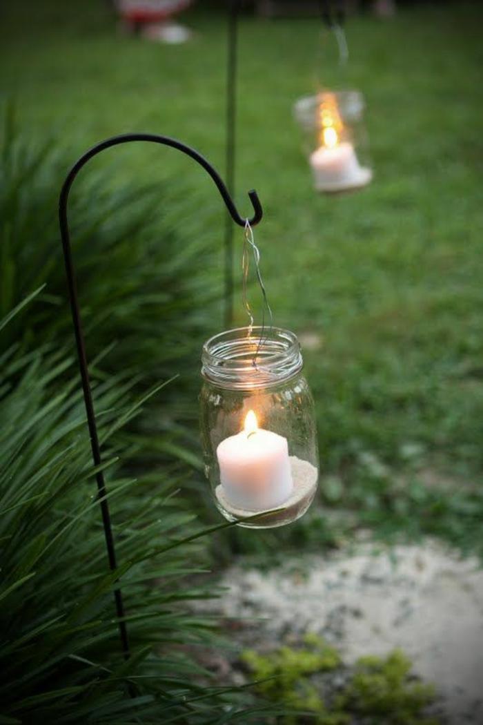 pots de confiture qui servent de bougeoirs pour illuminer la pelouse, déco jardin récup aux bougies blanches, ambiance magique