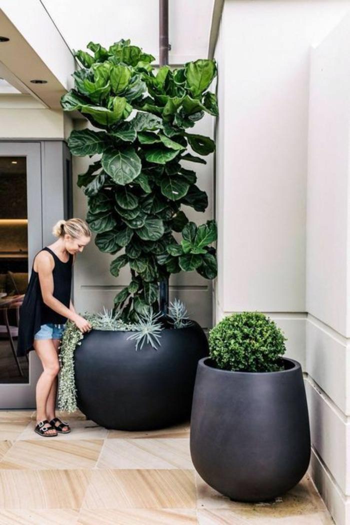 deux larges et hauts pots en céramique noire en forme ronde, decoration terrasse exterieur, decoration jardin terrasse, sol couvert de parquet de jardin et balcon